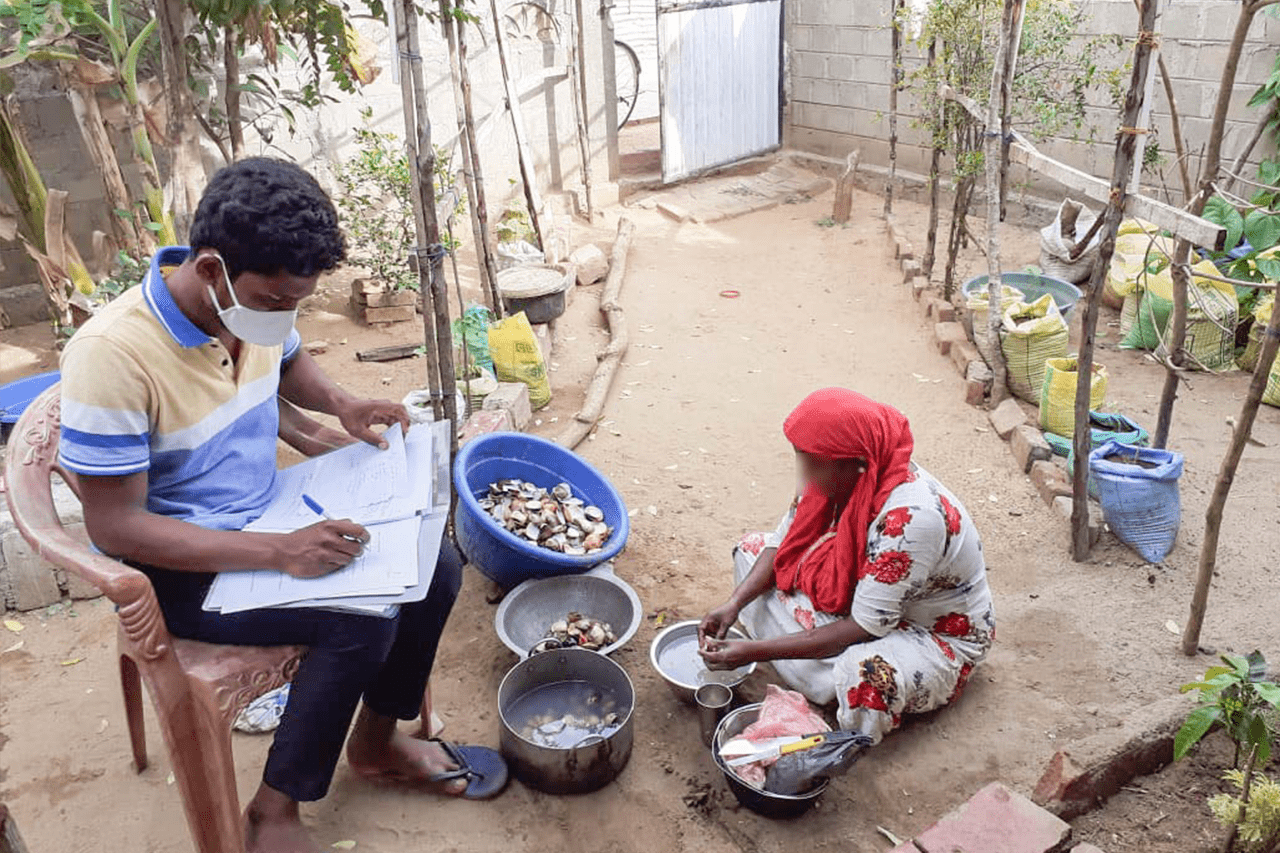 Mujas interviews a processor as she separates the shells of clams in Mutur